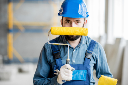 Portrait of a builder in working uniform holding yellow paint roll and grinding tool indoors