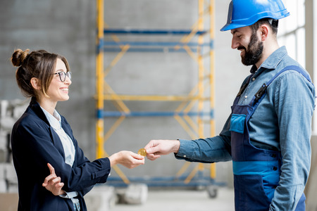 Businesswoman giving cryptocoin to builder as a salary for the work standing at the construction site Stockfoto