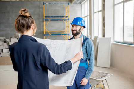 Foreman expertising the structure with businesswoman holding a blueprints at the construction site indoors Banque d'images - 99571237