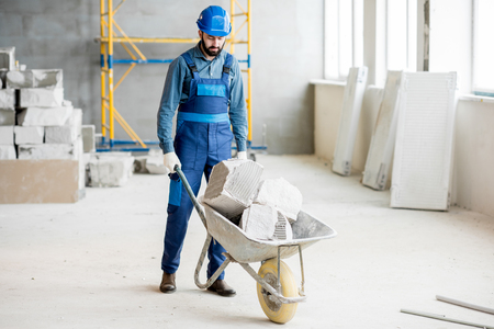Builder carrying blocks on a wheelbarrow at the construction site indoors
