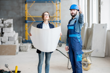 Foreman expertising the structure with businesswoman holding a blueprints at the construction site indoors Banque d'images - 99571251