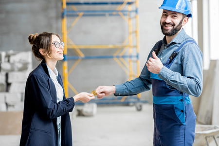 Businesswoman giving cryptocoin to builder as a salary for the work standing at the construction site Stok Fotoğraf