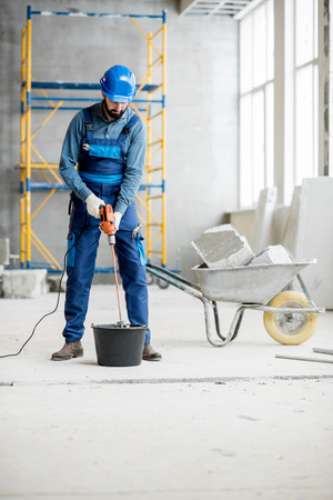 Builder in uniform mixing plaster with drill at the construction site indoors