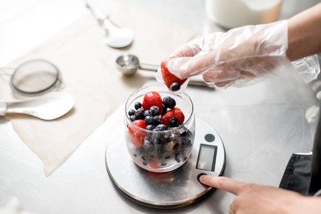 Putting berries into the small jar weighting ingredients for the ice cream production 스톡 콘텐츠