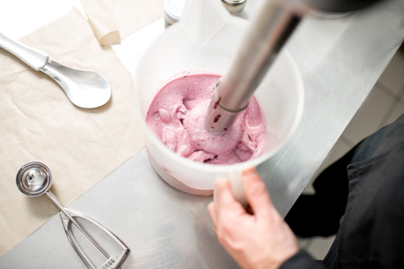 Mixing milk with sugar and berries for ice cream production