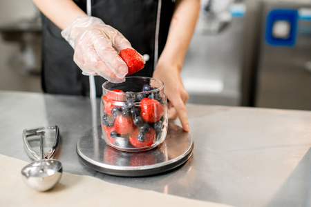 Putting berries into the small jar weighting ingredients for the ice cream production Stockfoto