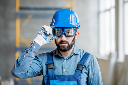Close-up portrait of a handsome bearded builder with protective glasses and helmet indoors Foto de archivo