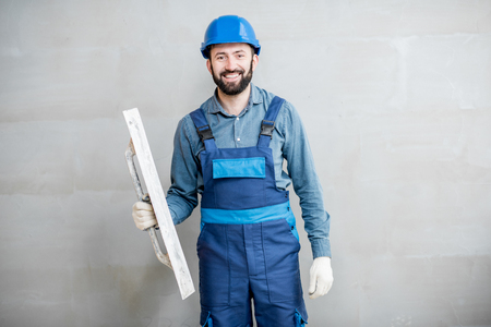 Portrait of a handsome builder in blue working uniform plastering the wall indoors Stock fotó
