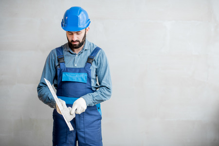 Plasterer in blue working uniform cleaning spatula standing on the grey wall background Stock Photo