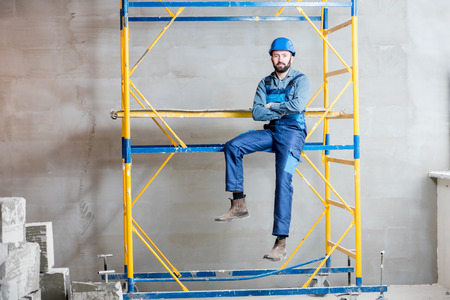 Builder in blue working uniform sitting on the scaffolding indoors 版權商用圖片