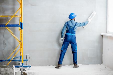Gipser in blauer Arbeitsuniform verputzt die Wand im Innenbereich Standard-Bild