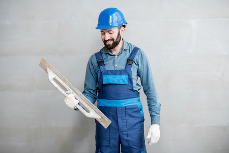 Portrait of a handsome builder in blue working uniform plastering the wall indoors Standard-Bild