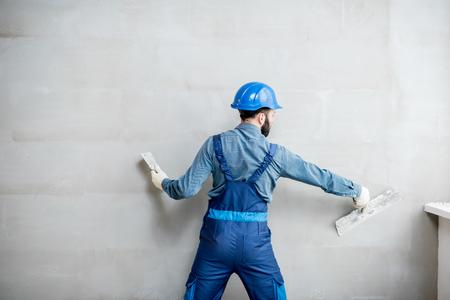 屋内の壁に石膏青い作業ユニフォームの石膏