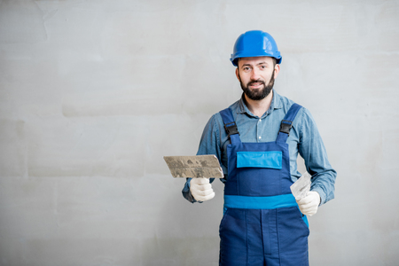 Portrait of a handsome builder in blue working uniform plastering the wall indoors Stockfoto