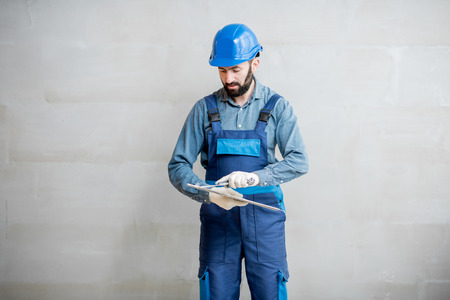 Plasterer in blue working uniform cleaning spatula standing on the grey wall background Zdjęcie Seryjne