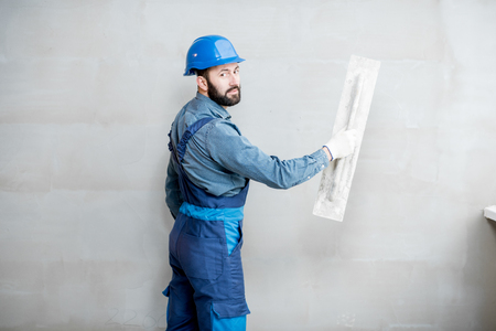 Portrait of a handsome builder in blue working uniform plastering the wall indoors Zdjęcie Seryjne