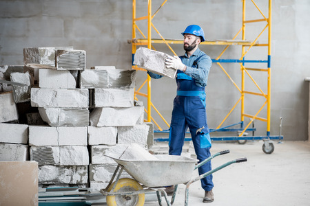 Builder in uniform working with building blocks at the construction site indoors Stok Fotoğraf