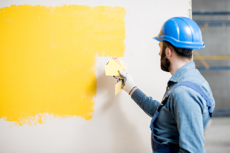 Painter in blue workwear comparing yellow painted wall with color swatches indoors Stock Photo