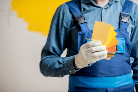 Painter in blue workwear holding color swatches on the yellow wall background indoors