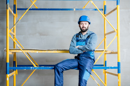 Builder in blue working uniform sitting on the scaffolding indoors Imagens