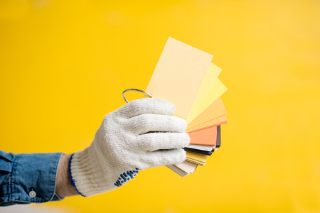 Holding color swatches on the yellow painted wall background