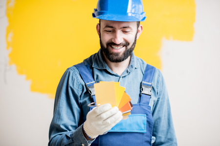 Painter in blue workwear holding color swatches on the yellow wall background indoors Reklamní fotografie - 98270678