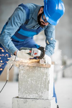 屋内の建設現場で切断機を備えた作業ユニフォーム切断金属プロファイルのビルダー