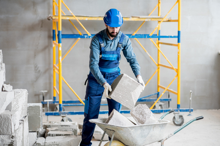 Builder in uniform working with building blocks at the construction site indoors Stockfoto