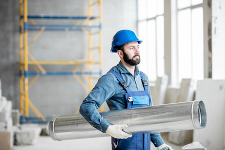Builder standing with ventilation pipe at the construction site indoors