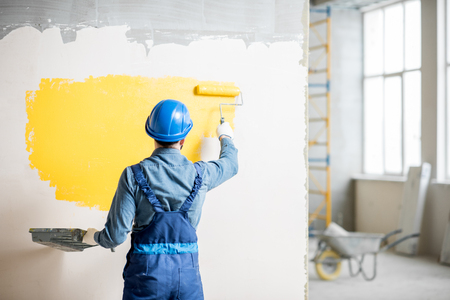 Workman in uniform painting wall with yellow paint at the construction site indoors Foto de archivo