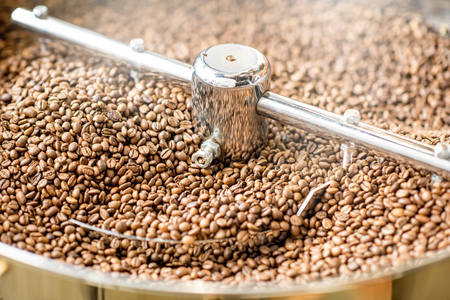 Close-up view on the roasted coffee beans cooling in the roaster machine