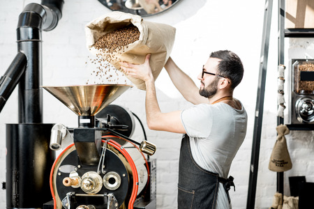 Man pouring coffee beans into the roaster machine indoors