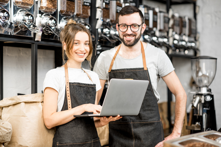 Coffee store owners or managers working with laptop standing at the counter of the shop Stock Photo