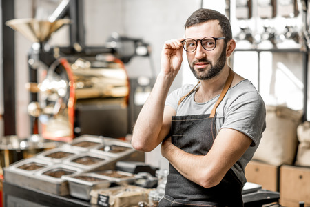 Portrait of a handome bearded barista in uniform standing in the coffee shop with coffee roaster machine on the bckground Stockfoto