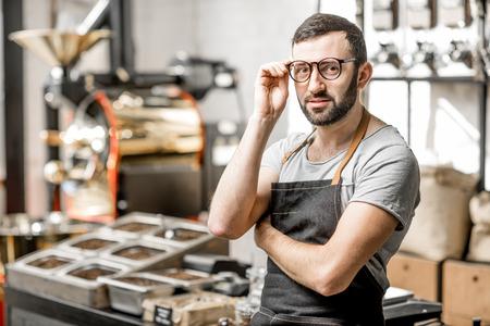 Retrato de un barista barbudo handome en uniforme de pie en la cafetería con cafetera tostadora en el bckground Foto de archivo