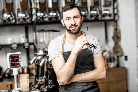 Portrait of a handome bearded barista in uniform standing in the coffee shop