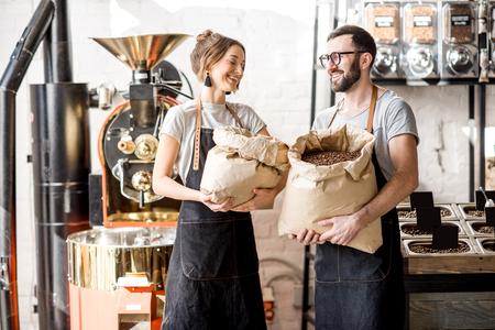Retrato de dos felices baristas en uniforme de pie con bolsas llenas de granos de café en la cafetería. Foto de archivo