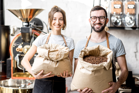 Portrait of a two happy baristas in uniform standing with bags full of coffee beans at the coffee store 版權商用圖片 - 98439050