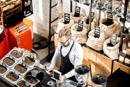 Sales man standing at the counter in the coffee store with roaster machine on the background