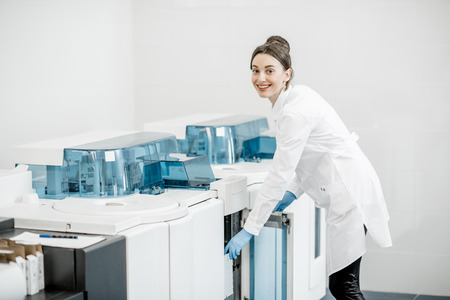 Woman technician expertising analyzer machine in the laboratory Banco de Imagens