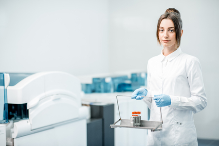 Portrait of a woman technician standing with test tubes in the laboratory Stock Photo