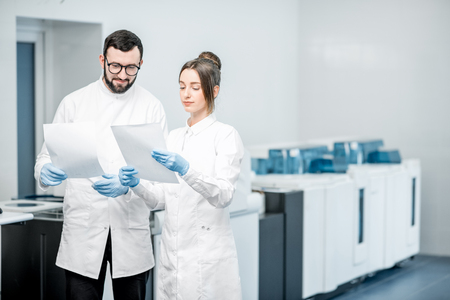Couple of medics working with paper documets standing in the laboratory with analyzer machine on the background Stock Photo