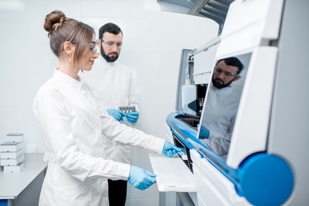 Laboratory assistants in unifrom working with professional medical analizer at the laboratory Stock Photo