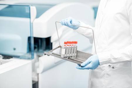 Laboratory assistant holding test tubes near the analyzer machine