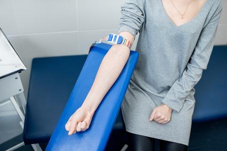 실험실에서 팔 정맥에서 혈액 검사를받는 동안 젊은 여성 환자