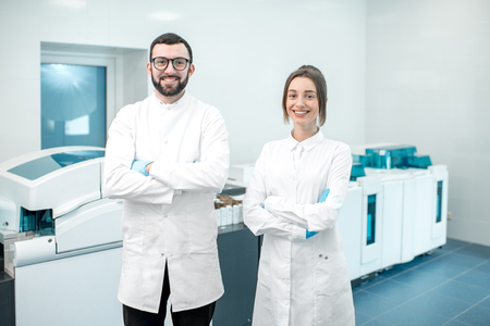 Portrait of a couple of medics standing in the laboratory with analyzer machine on the background