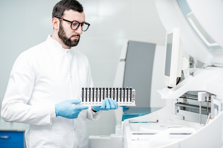 Male laboratory assistant in uniform holding test tubes near the analizer machine at the laboratory