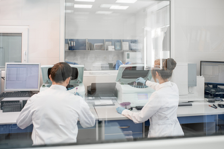 View through the glass on the laboratory with medic doing analysis