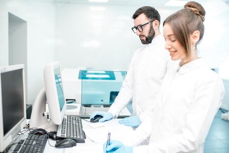 Couple of medics configuring analyzer machine in the modern laboratory
