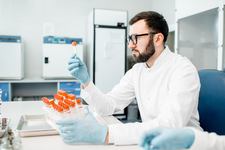 Male laboratory assistant examining test tube in the bacteriological department of laboratory
